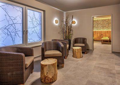 Im Ruhebereich sitzen Wellness Sauna Saunalandschaft Dekoration Sitzecke Baumstamm Tisch Baumscheiben Licht Lampe Leuchte